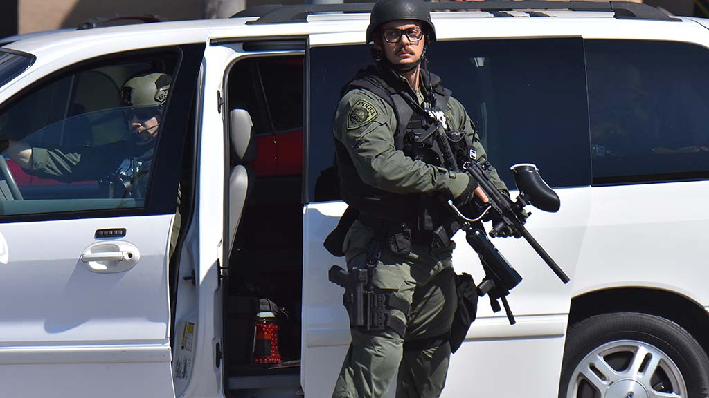 A member of the La Mesa Police Department surveys the scene after getting out of one of several unmarked vans.