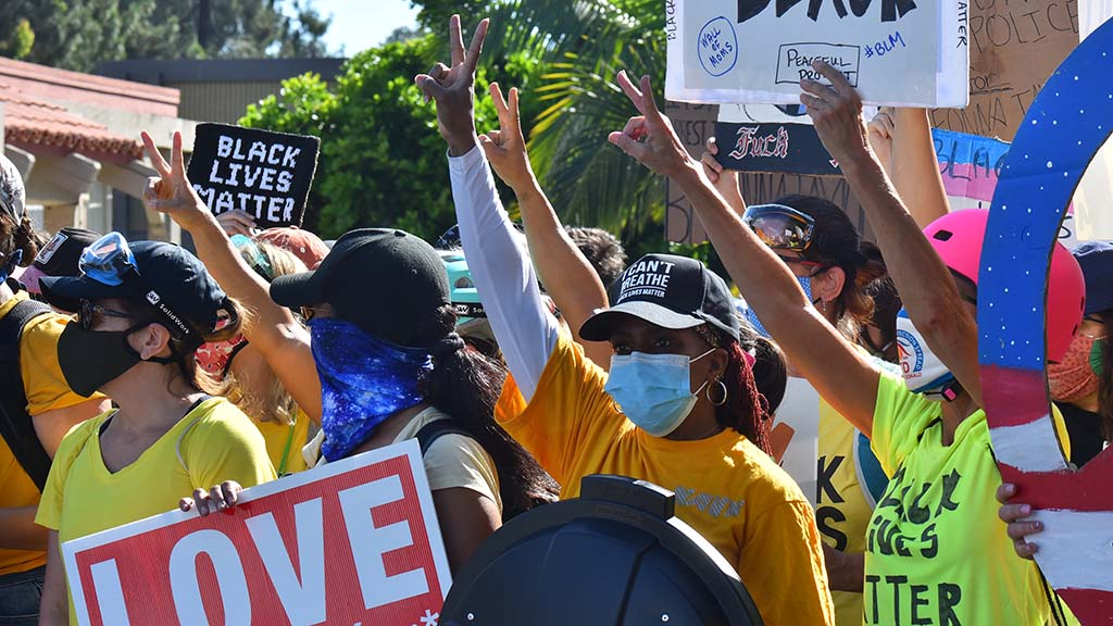 Protesters respond with peace signs and shouts of love toward counterprotesters in La Mesa.