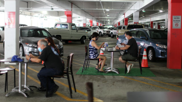 People eat lunch in a parking lot amid the pandemic