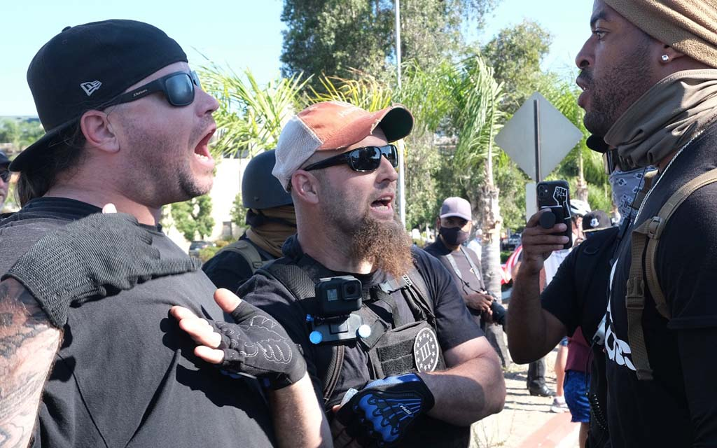 Ryan McAdams of Jamul (left) was later arrested on battery and other charges after a clash with protesters. Here he and Kris Wyrick of Alpine (center) exchange words before march with an unidentified protester.