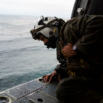 Marine scans water from helicopter