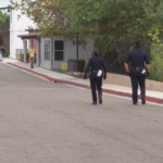 San Diego police walk toward teen suspected of displaying gun during a Zoom session.