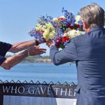 World War II veteran Al Hansen (left) and Mac McLaughlin, president and CE) of USS Midway Museum, toss a wreath into the sea from aboard the USS Midway.