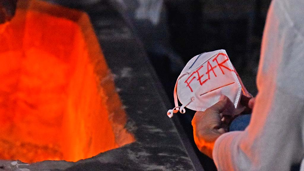 Genevieve Peters writes fear on a KN 95 mask before burning it during a anti-mask protest.