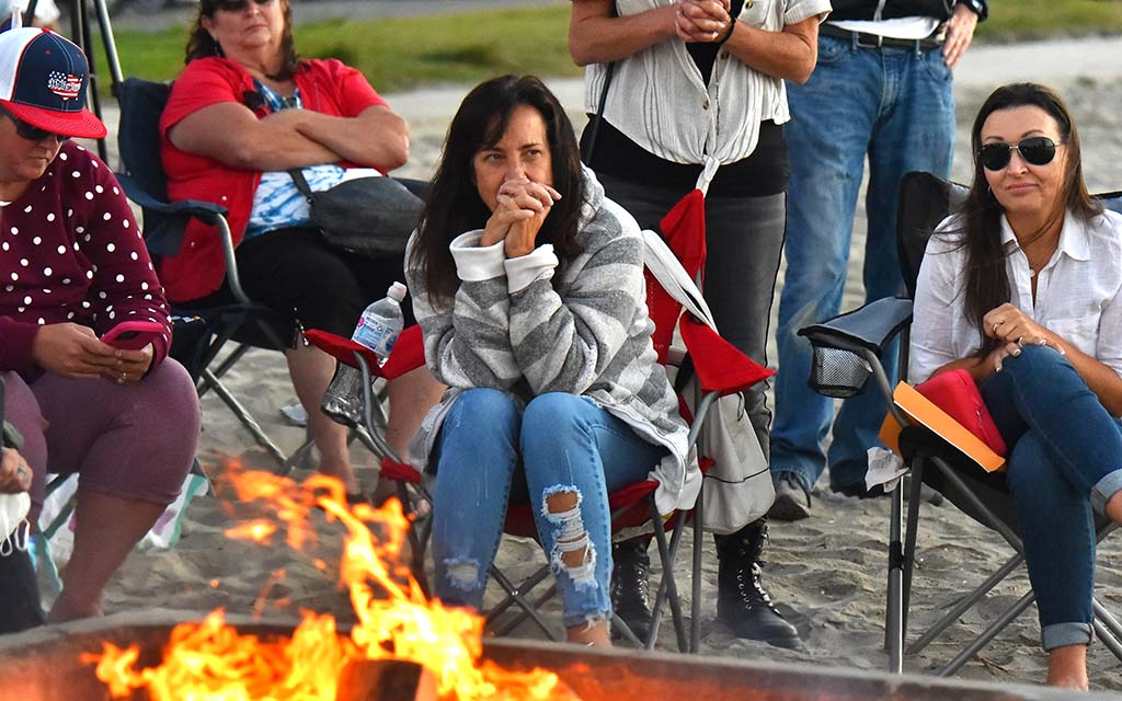 About two dozen people, all but one without a mask, gathered to listen to speakers and burn masks in Mission Bay.