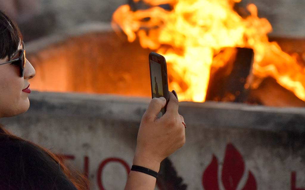 An anti-mask proponent records speeches by a fire in Mission Bay.