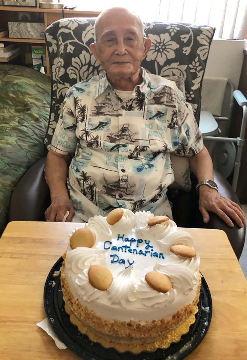 Granddaughter Khanh Le snaps a photo of her 109-year-old grandfather, Khen Ngo, and his cake as the family celebrates National Centenarian Day, which occurs on Sept. 22.