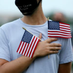 An activist holds American flags over his heart