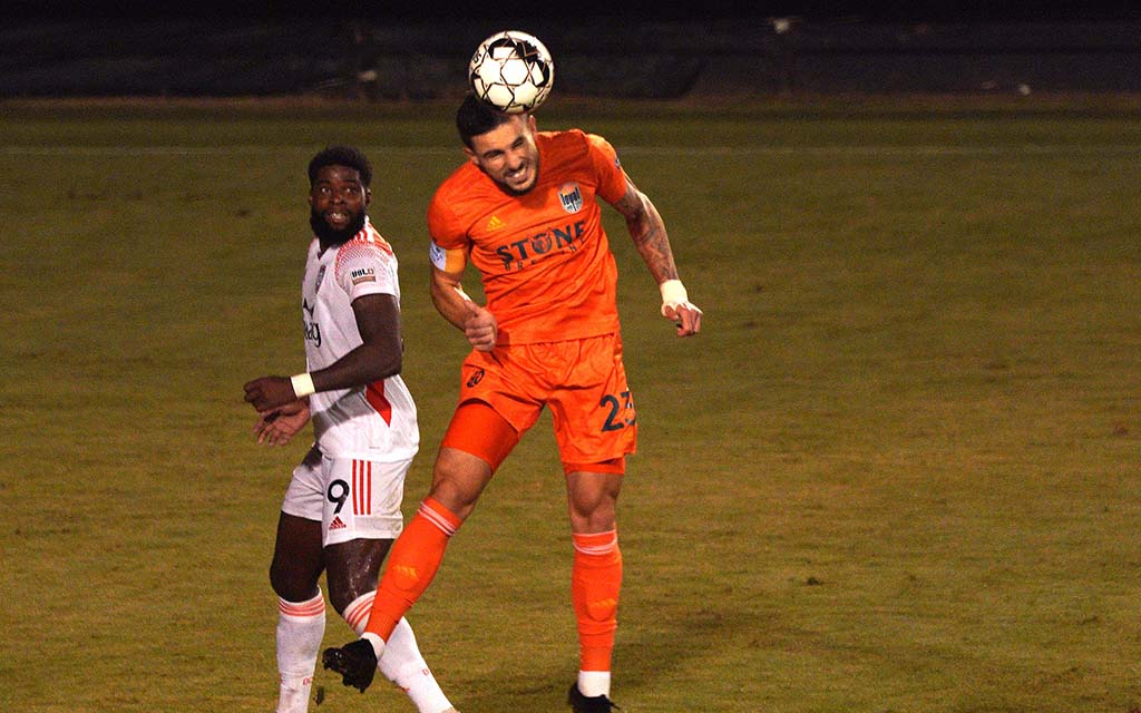 Loyal player Emrah Klimenta does a header in the second half to steer the ball against Orange County.