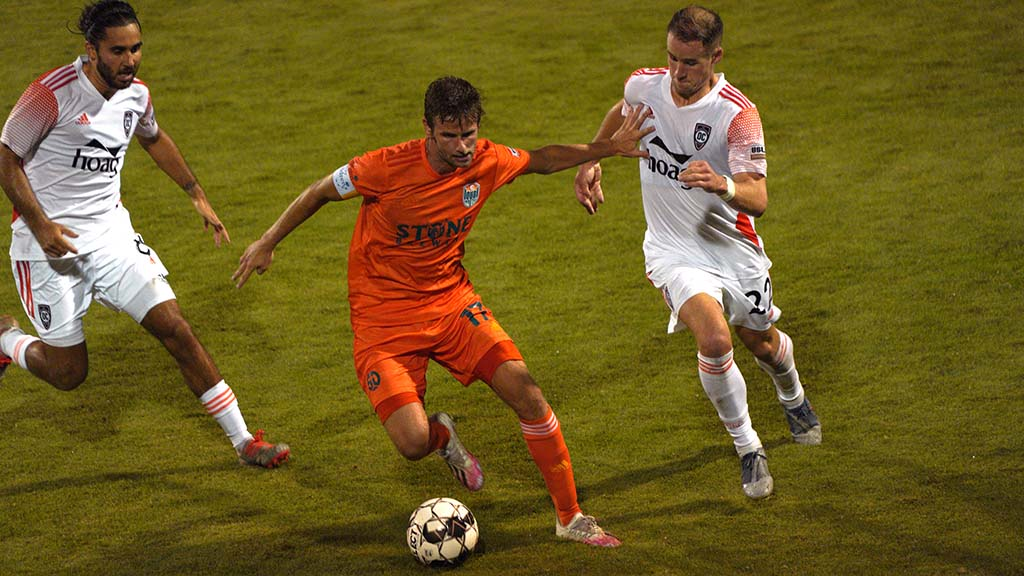Loyal player controls the ball amid Orange County pursuers.