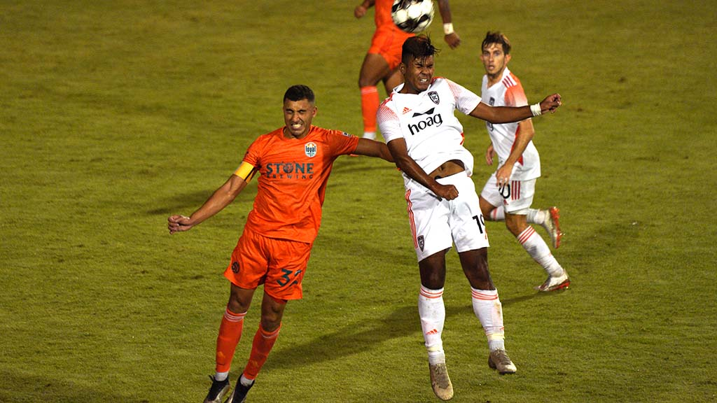 Loyal player Tarek Morad leaps as Orange County player Cammy Palmer heads the ball.