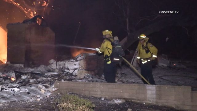 Firefighters cool down remains of a home