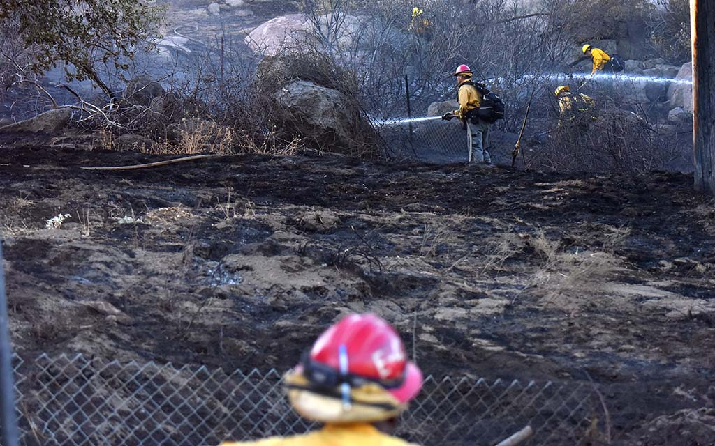 Firefighters mop up and douse remaining hot spots at brush fire that threatened possibly vacant home.