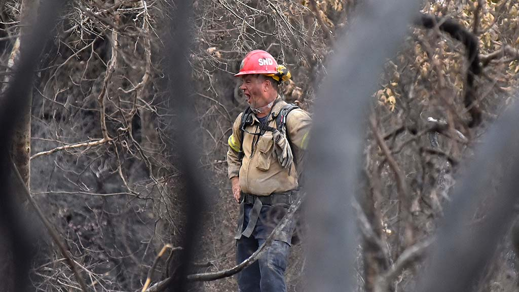 A member of a fire strike team that had fought the Valley fire for six days yawns at the end of a 12-hour day.