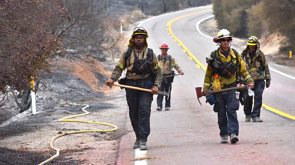 Members of a strike team return to trucks after a 12-hour day on the sixth day of firefighting in the Valley Fire.