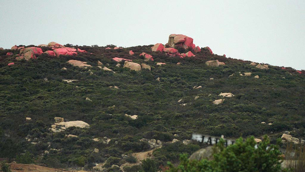 Hillsides spotted with fire retardant are seen in areas close to Alpine.