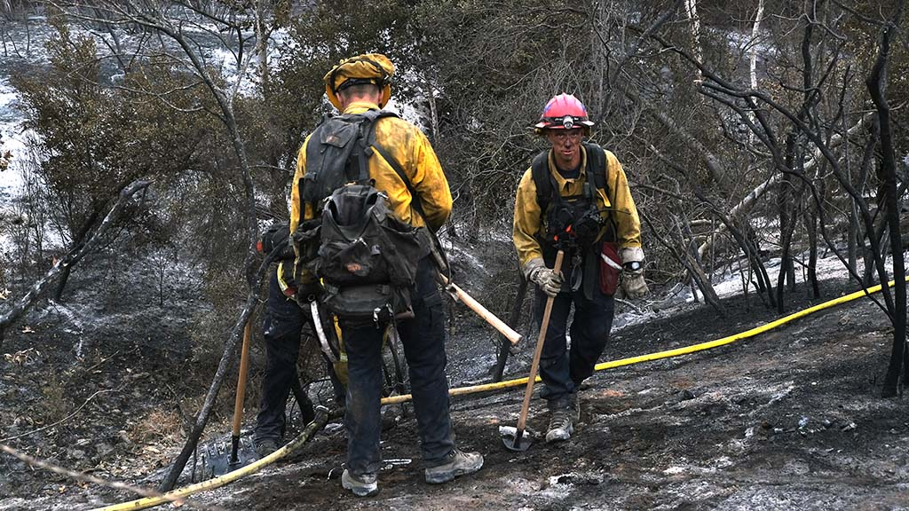Members of a strike team mops up after firefighting for six days in the east county.