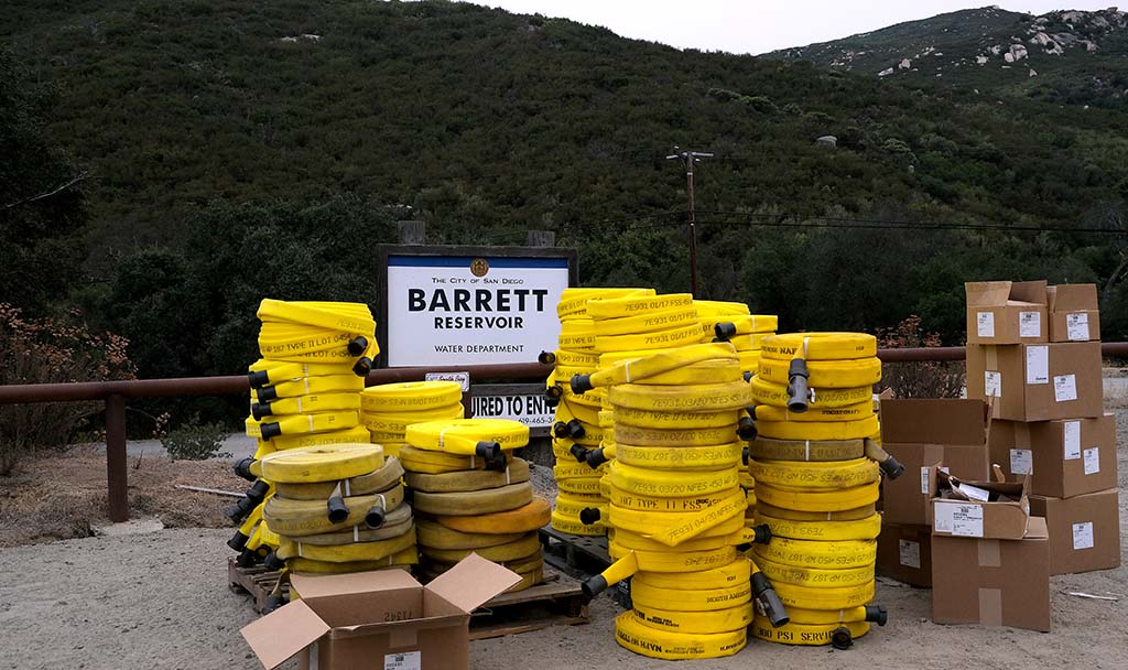 Firehoses are stacked up by the Barrett Reservoir as firefighters worked a sixth day to put out remaining hot spots.