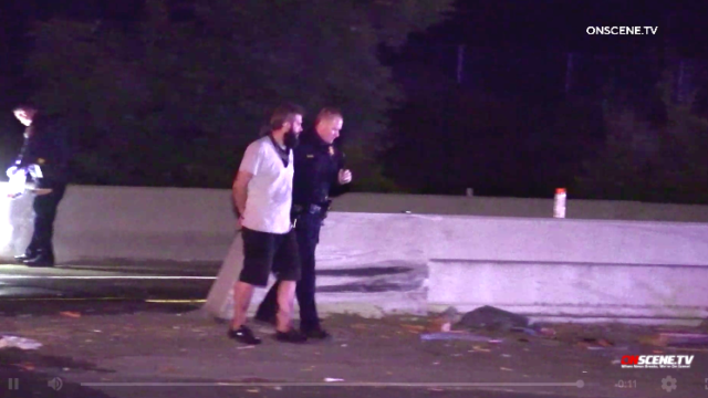 Suspected driver of pickup truck that crashed into tow truck is led away in handcuffs.