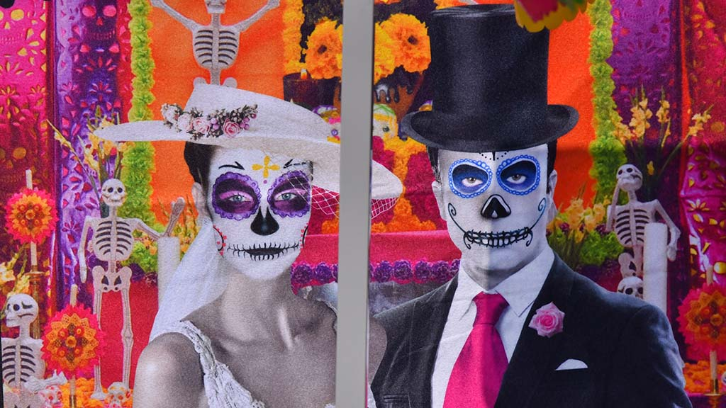 Paintings and wall hangings decorate the altars at the City Heights Día de los Muertos observance