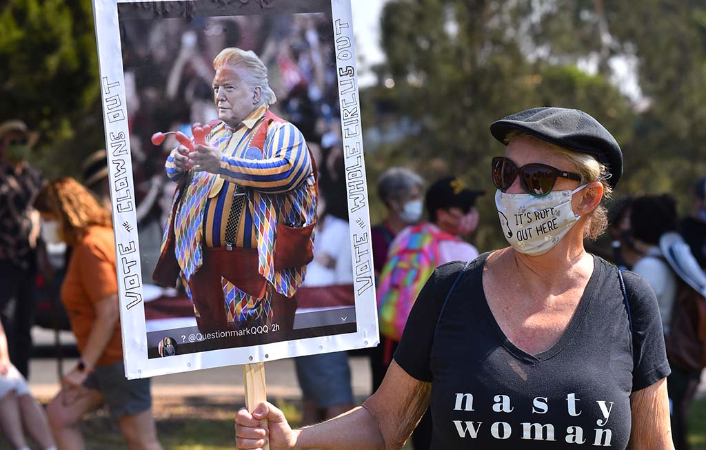 A women holding a sign depicting Donald Trump as a clown, attended a women's rally in Balboa Park.