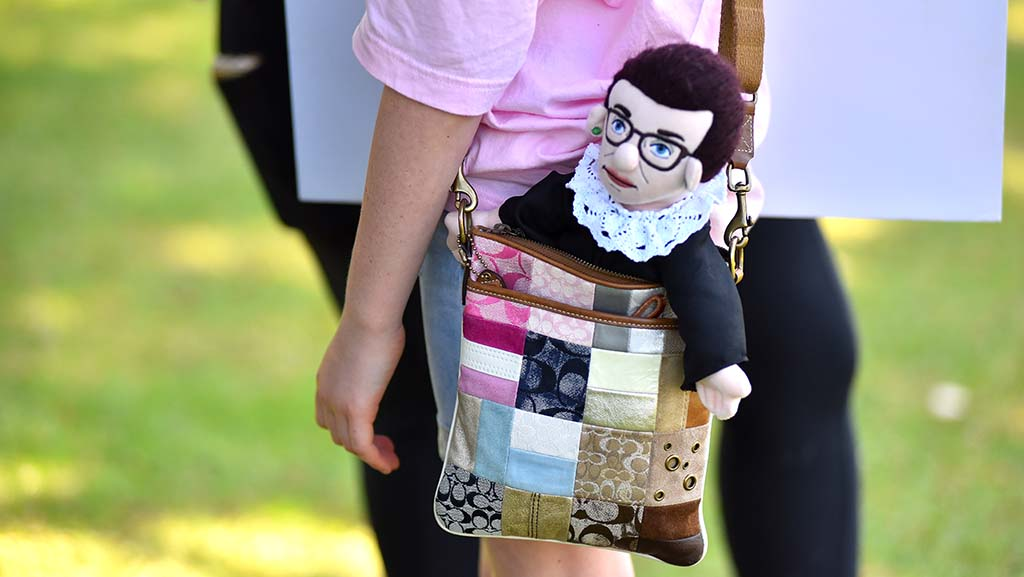 A girl carries of doll of the late Supreme Court Justice Ruth Bader Ginsburg at a women's protest in Balboa Park.