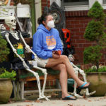 A woman wearing a surgical masks sits next to Halloween decorations