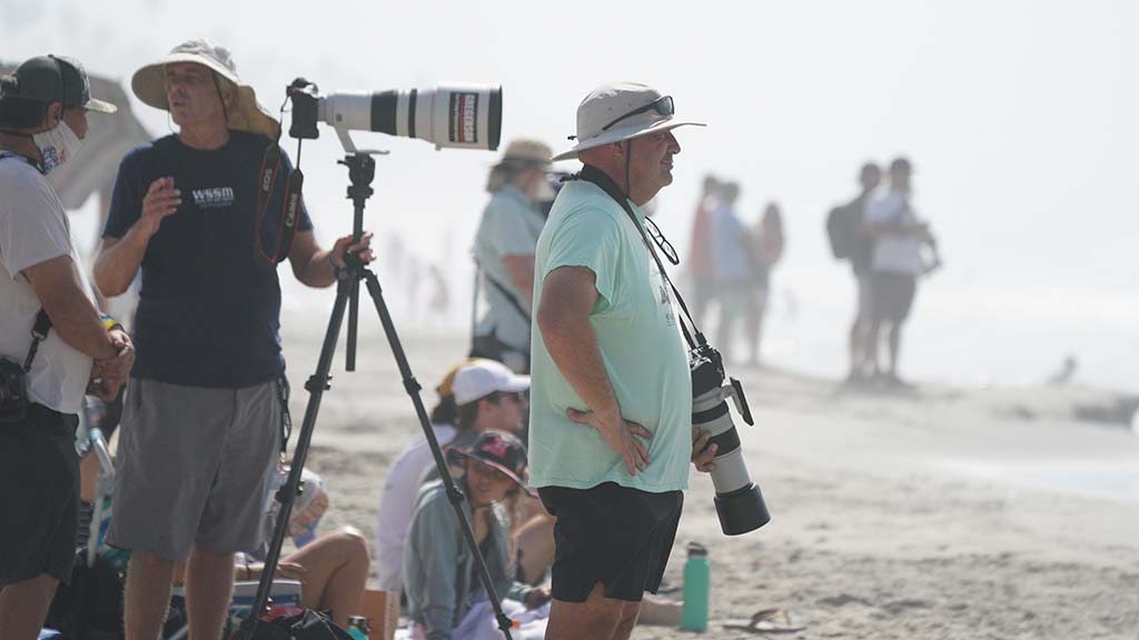 Photographers stand and wait as waves fail to materialize for extended periods.