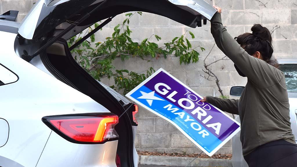 Heidi Martinez, loads a Todd Gloria lawn sign into a volunteer's car.
