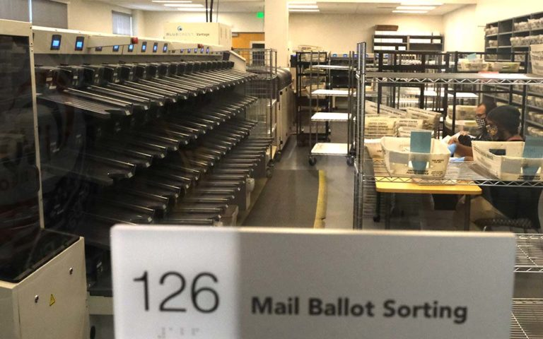 In the first step, stacks of mail-in ballots are scanned for voter signatures.