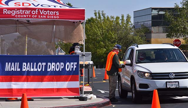 Voters stop by to drop off their mail-in ballots at the Registrar of Voters office in Kearny Mesa.