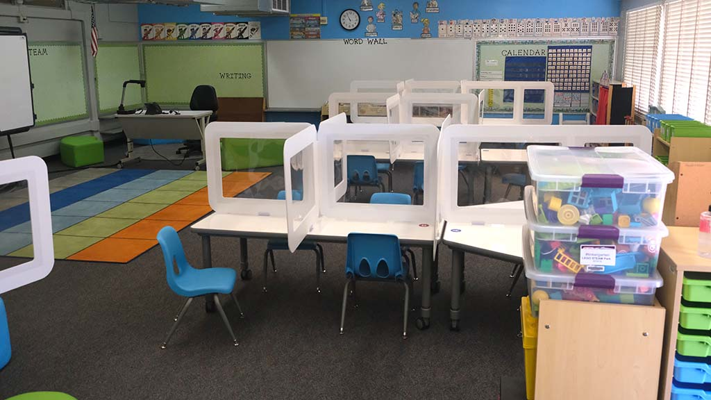 Classrooms are set up with plastic dividers for future phases of school openings.