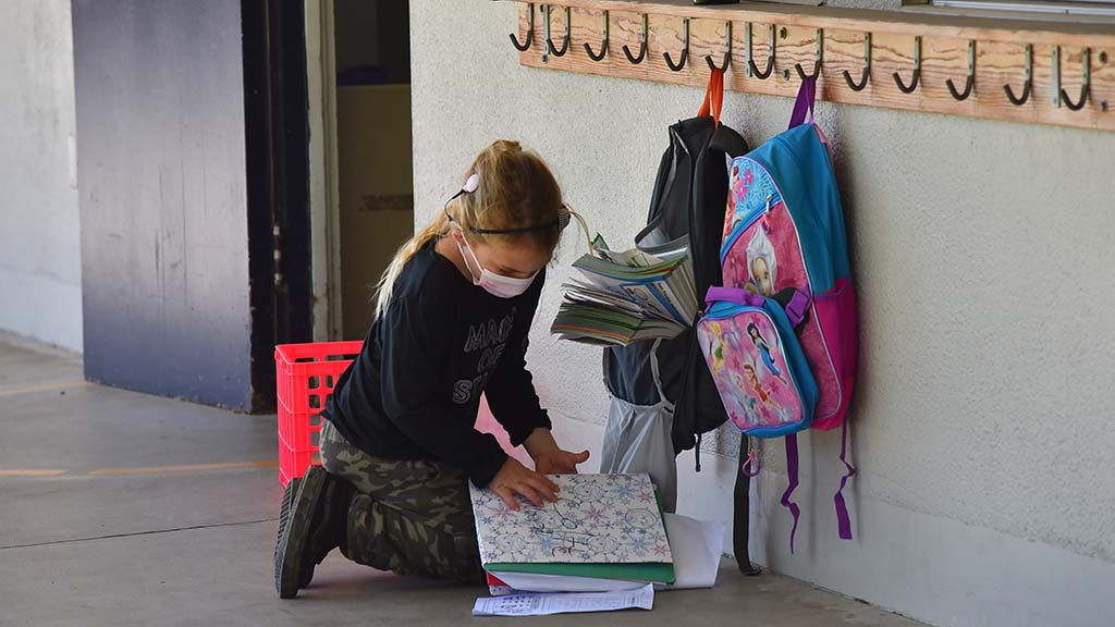A girl gets her school work together outside a classroom at Lafayette Elementary School in Clairemont on the first day of school since March.
