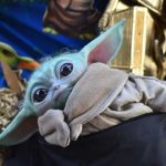 A Baby Yoda replica peers out of pouch of Dude Vader, Christopher Canole of La Jolla.