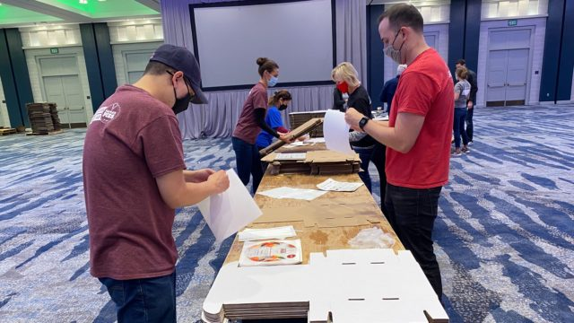 Volunteers assemble pie boxes.