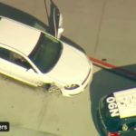 A Chevy Malibu that led 45-minute chase, surrounded by police vehicles, shows tire missing at Lindbergh Field.