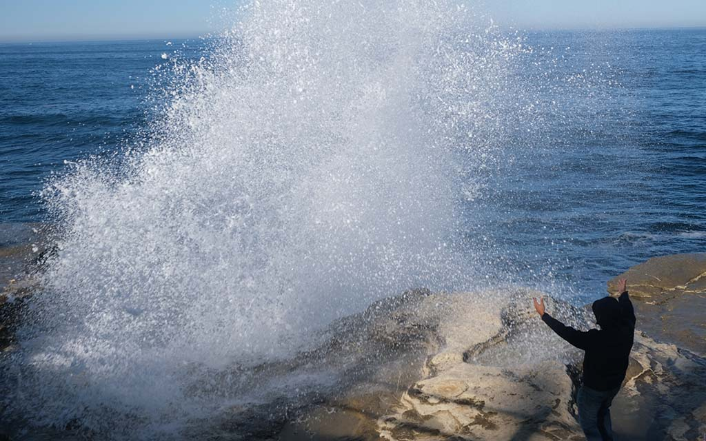 A man welcomes the rising spray as 7.5-feet tides moved into San Diego.