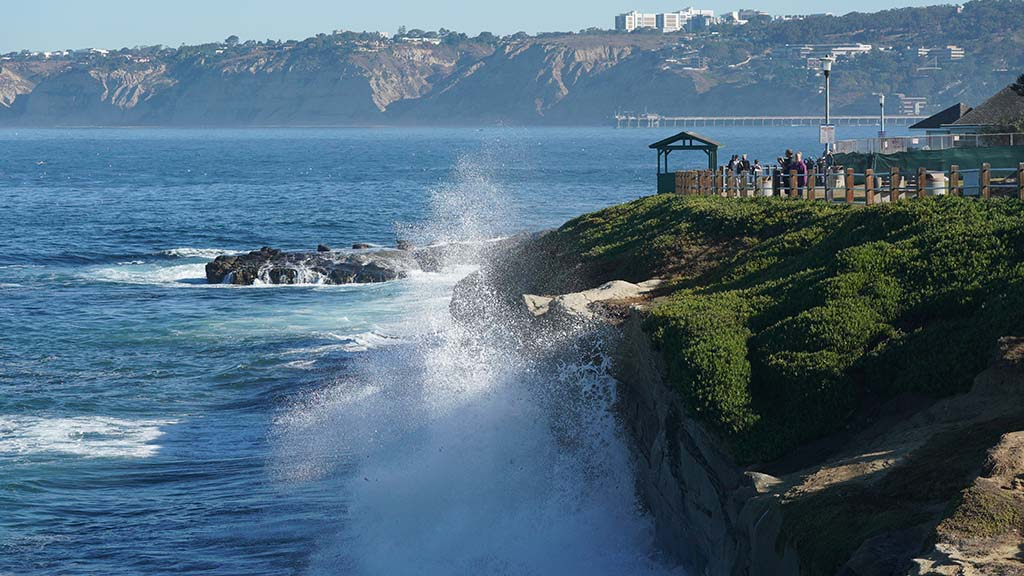 7.5-foot waves crash into La Jolla cliffs on the first day of King Tides while people watch.