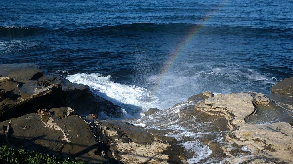 A rainbow forms in the spray of water hitting La Jolla rocks on the first day of King Tides.