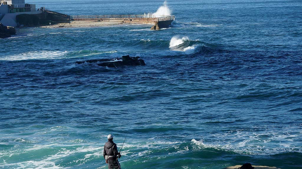 Waves slam into a sea wall as a fisherman hopes his bait lands him a big one.