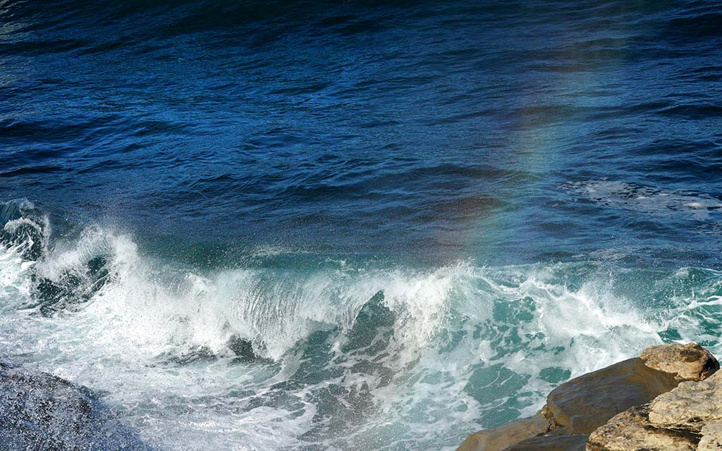 A rainbow forms in the spray of sea water during 7.5-foot tide during King Tides in La Jolla.