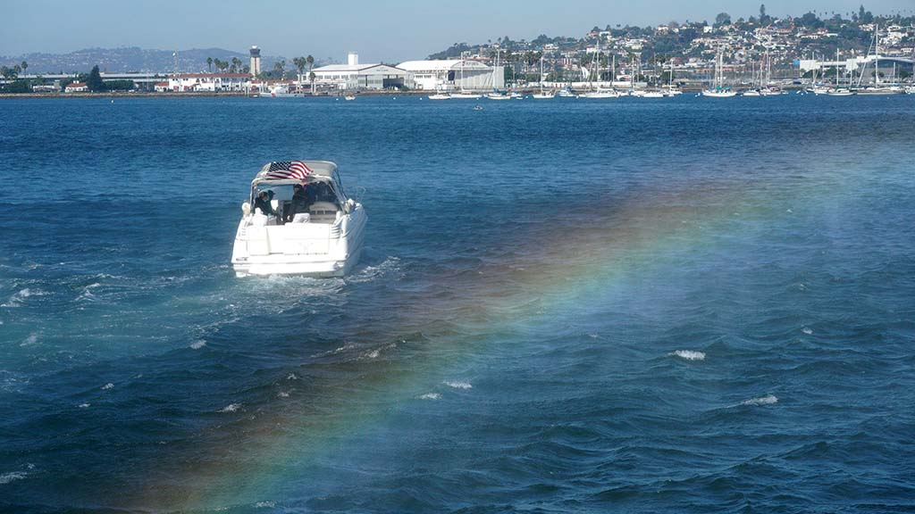 Downwash from a USS Coast Guard helicopter creates a rainbow near a boat at the Broadway Pier.