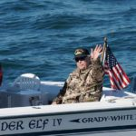 A veteran waves to spectators in a Veterans Day