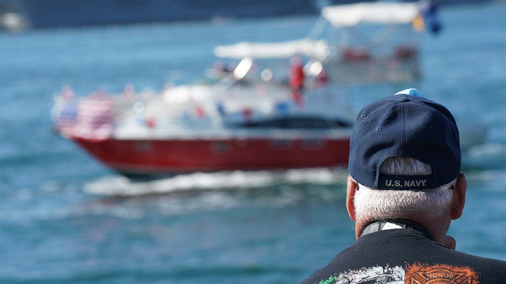 A Navy veteran watches one of dozens of boats in a parade on San Diego Bay on Veterans Day 2020.