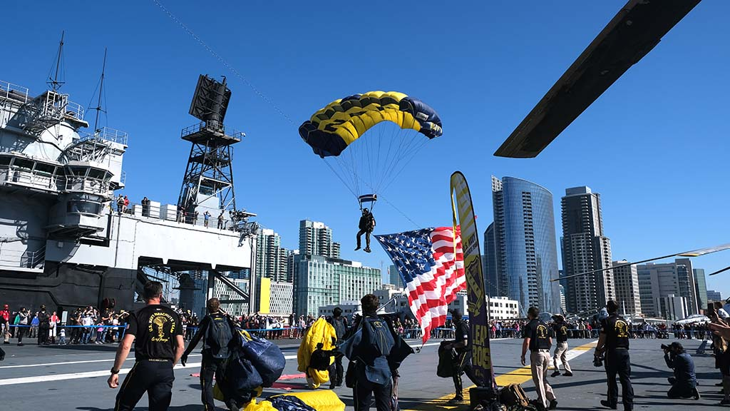 A member of the Navy Leap Frog Parachute Team lands on the flight deck of the USS Midway.