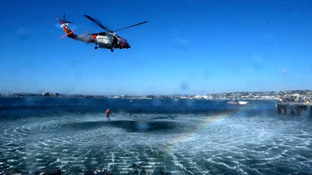 A USS Coast Guard helicopter lifts a diver and creates downwash on the San Diego Bay during a rescue demonstration.