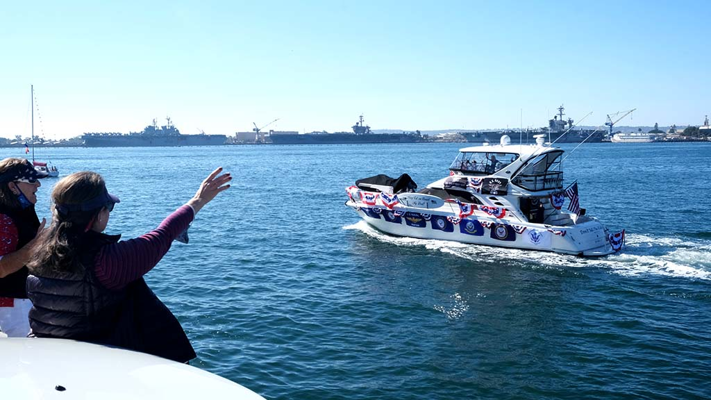 Spectators in the USS Midway parking lot wave to boats in a parade in the bay on Veterans Day 2020.