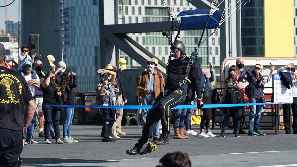 A Leap Frog parachutist is about to touch down in front of a crowd aboard the USS Midway on Veterans Day 2020.