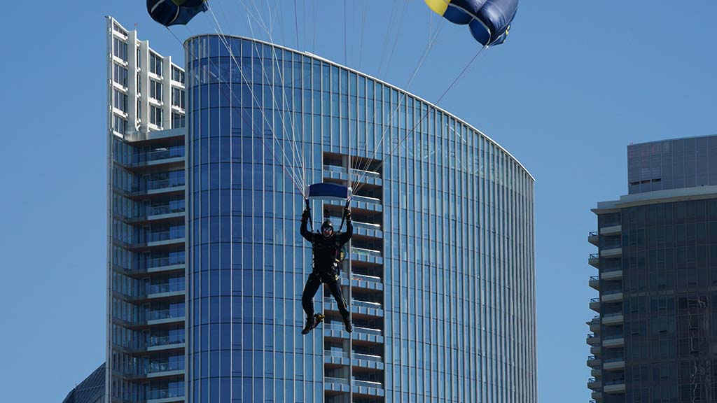 A member of the Navy Leap Frogs descends onto the USS Midway as part of Veterans Day events amid a pandemic.