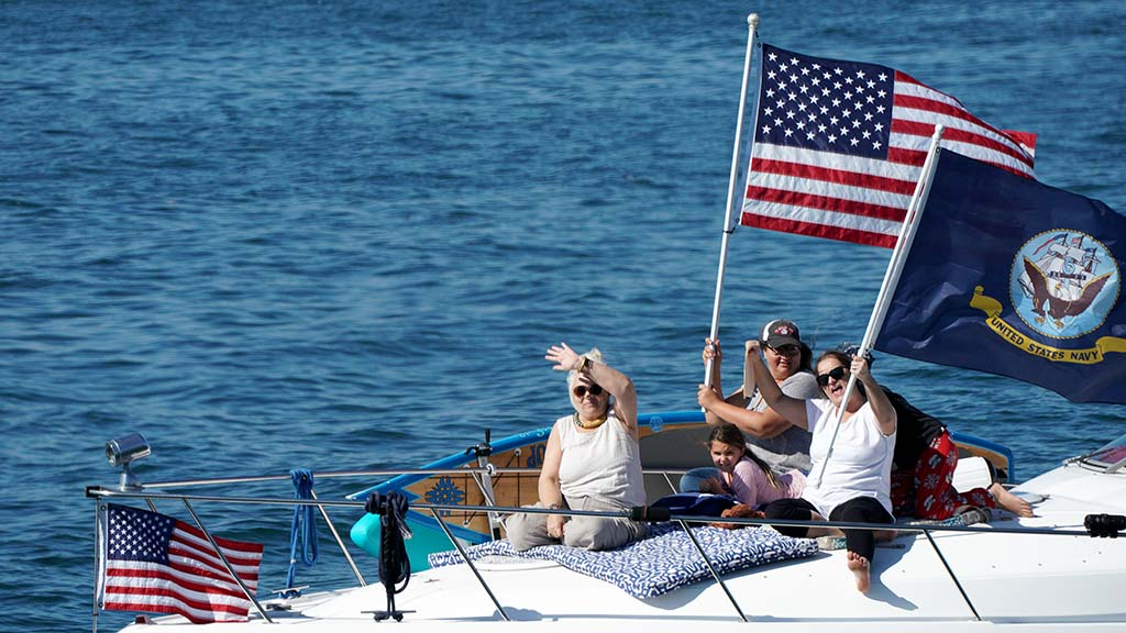 Boaters wave to spectators near the USS Midway during a boat parade in San Diego Bay on Veterans Day 2020.